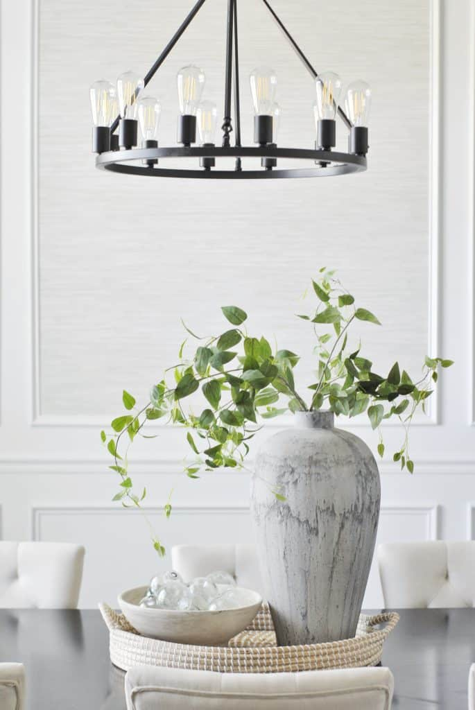 white wall with black chandelier and picture frame molding vase in front on table with greenery