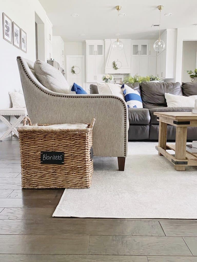 rustic coffee table with cream rug and dark hardwood floors with wicker basket for blankets next to an arm chair