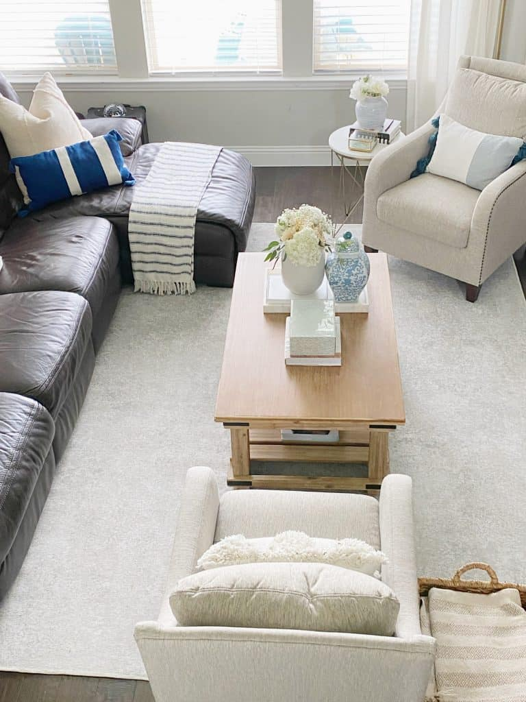 overhead view of living room including cream rug, rustic coffee table, cream arm chairs and brown leather couch