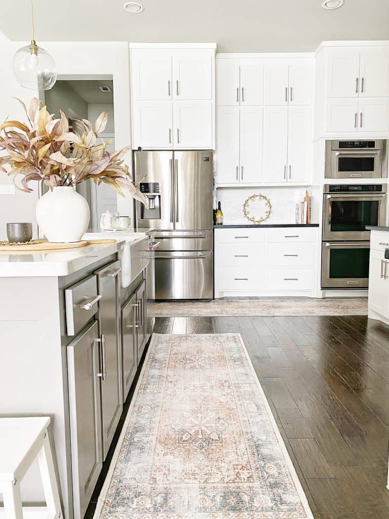 white kitchen with stainless steel fridge and 2 vintage runner rugs