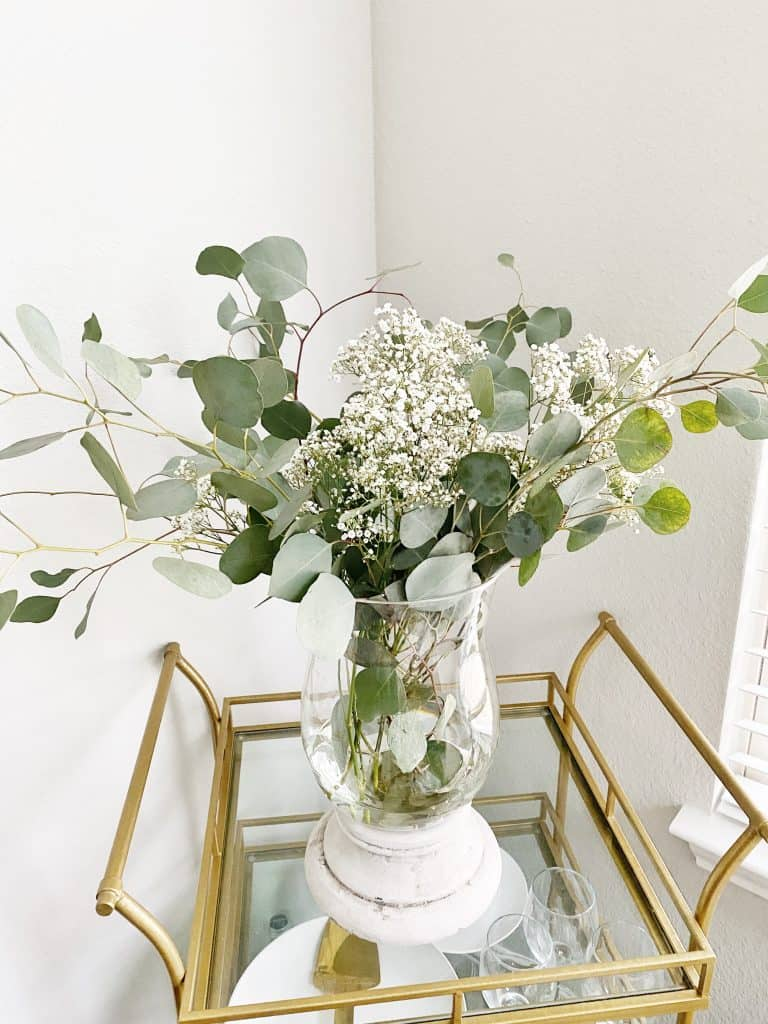 floral arrangement in clear vase on gold and glass bar cart