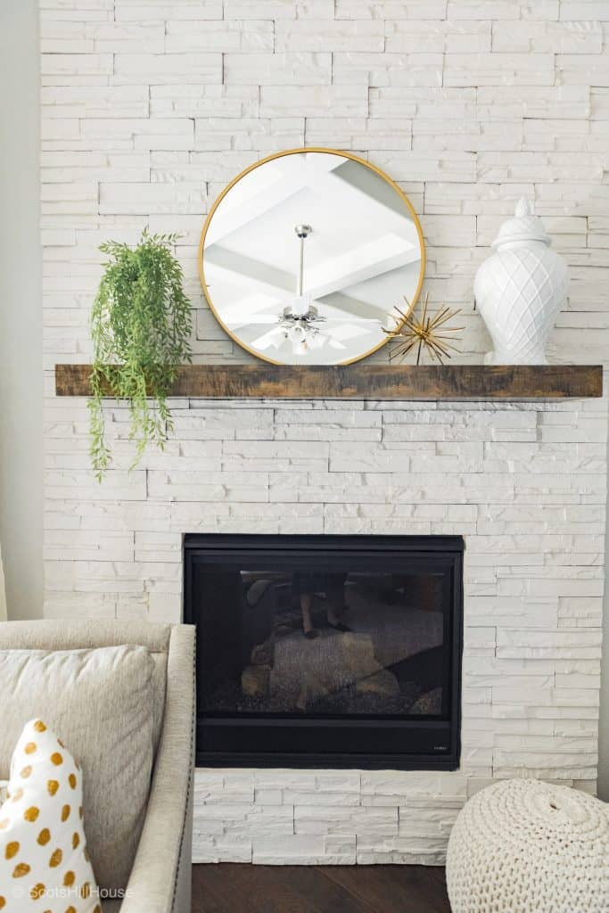 white brick fireplace with wood mantle and gold mirror, white vase and greenery