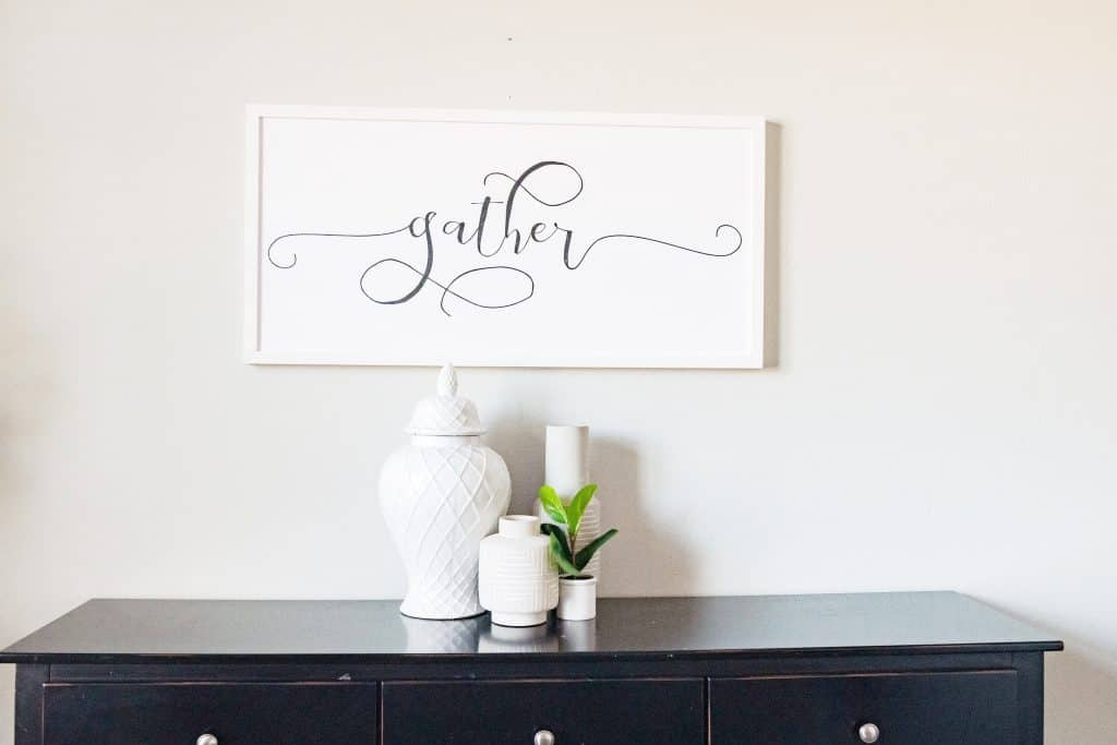 black console table with small vases and gather sign hanging over the table