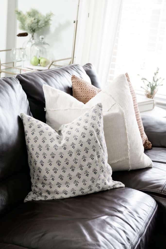 brown leather couch with 3 accent pillows in neutral coordinating colors