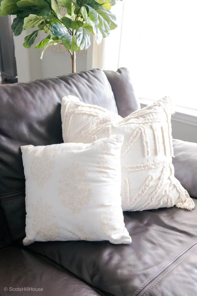 brown leather couch with 2 white accent pillows