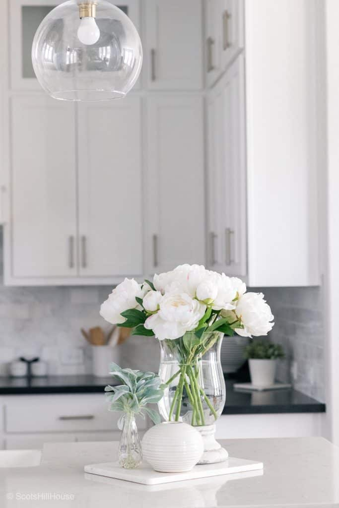 white kitchen with white countertops and white flowers in a vase on counters