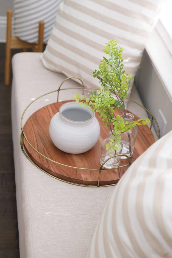 round wood tray with white vase and 2 small glass vases with single stem greenery