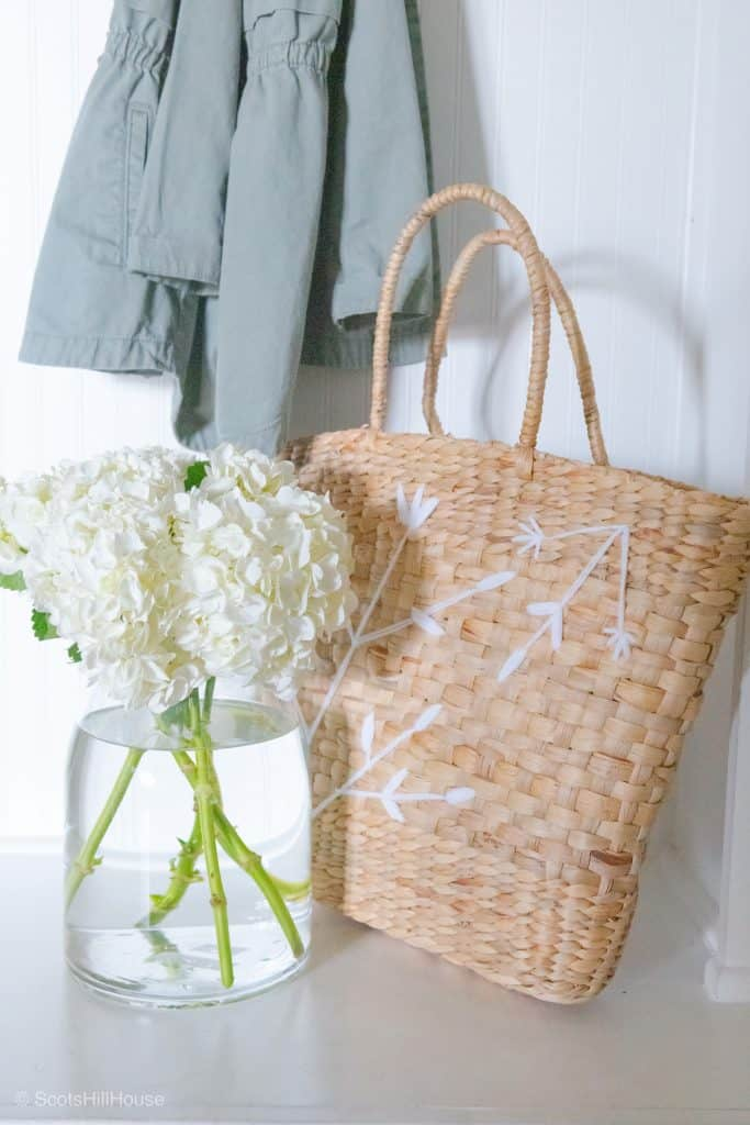 wicker handbag and hydrangeas in a clear vase with coat hanging in the background
