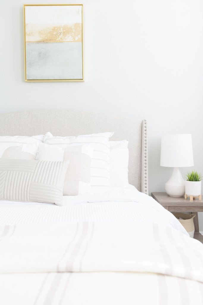 white walls, white bedding and neutral side table