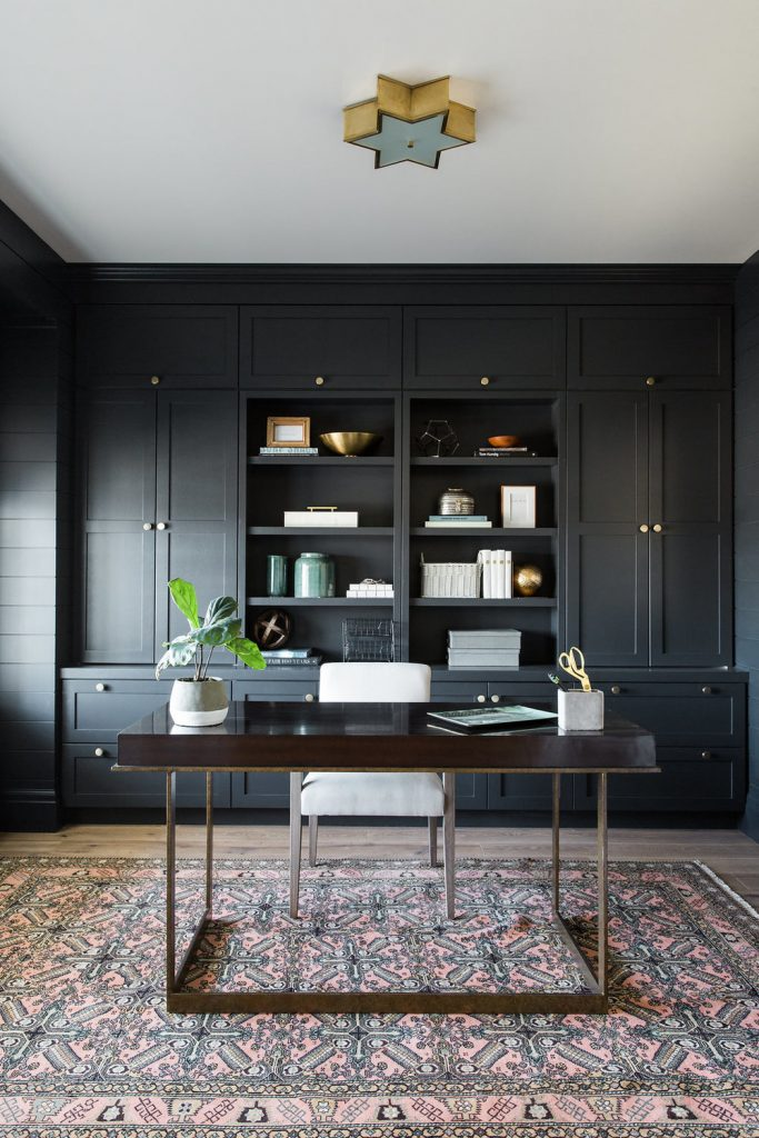 sherwin williams black cabinets in office with wood desk and vintage rug